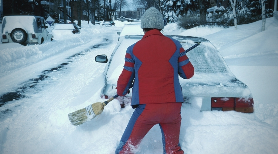 Woman clearing out snow from a car using broom