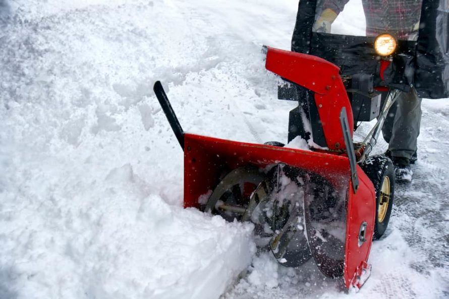 Winter season fun: Man removing snowstorm aftermath with a bright red snowblower.