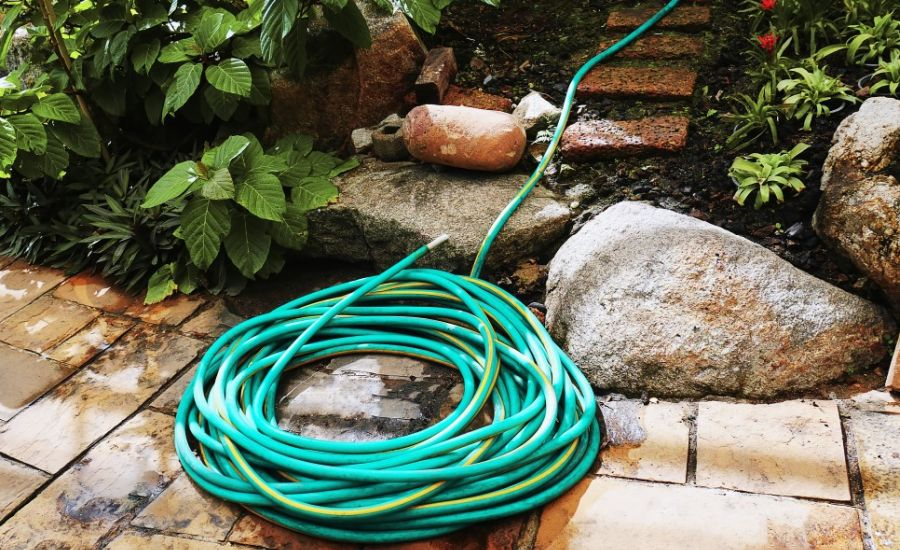 Rolled up green garden hose without kinks lying on a walkway next to a garden bed.