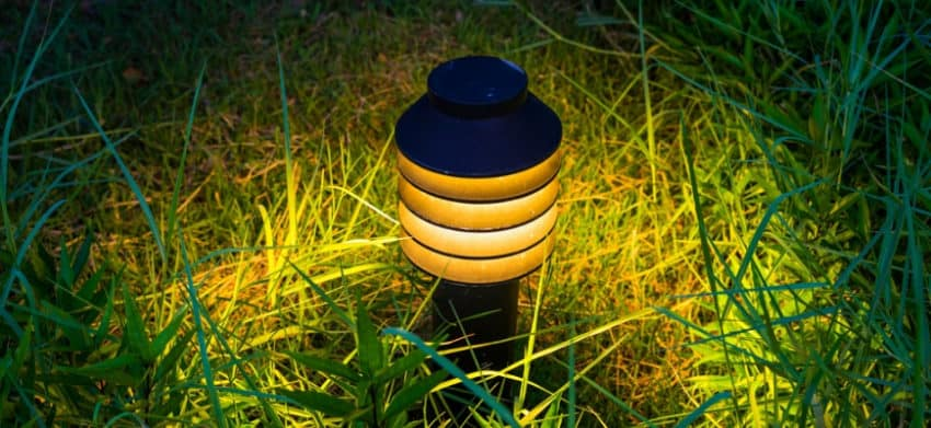 Lighted solar light mounted to ground.