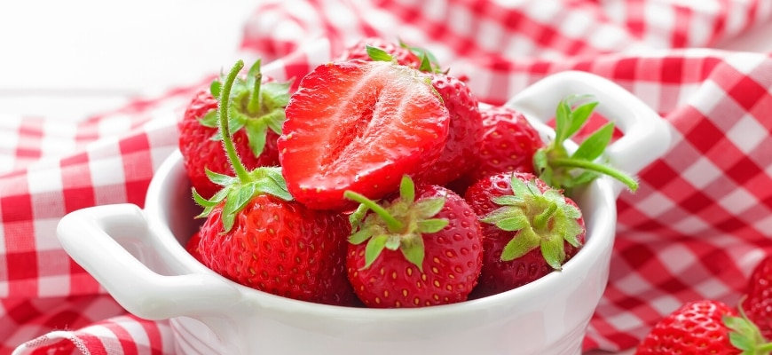 Strawberries on cup,top with half sliced and laid on a checkered red and white cloth.