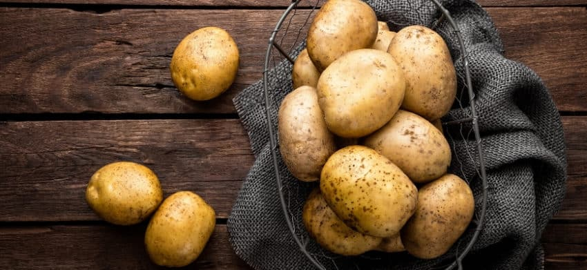 Potatoes on strainer laid on top a gray cloth.