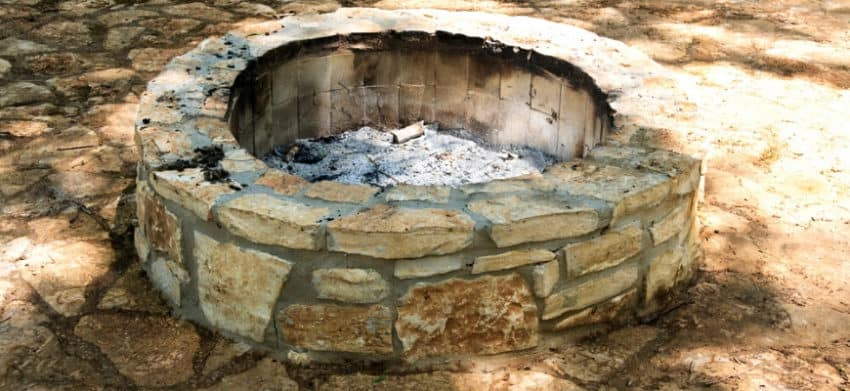 An empty stone fire pit with just ashes left