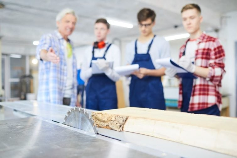 Group of men looking at a table saw