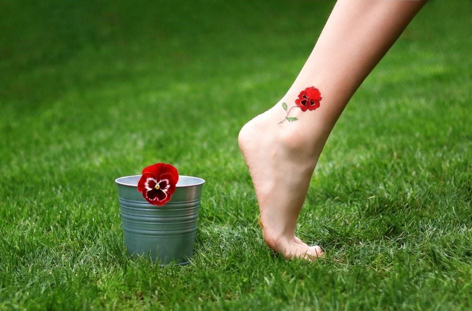 Barefoot girl walking outdoor on green grass