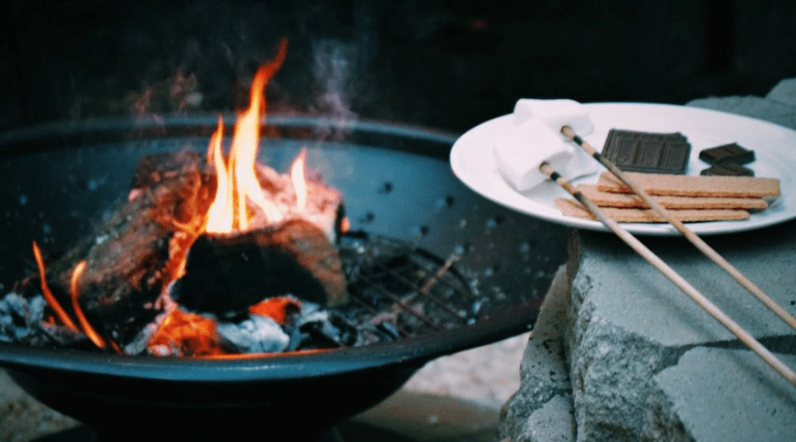 smores and a burning fire in a portable firepit