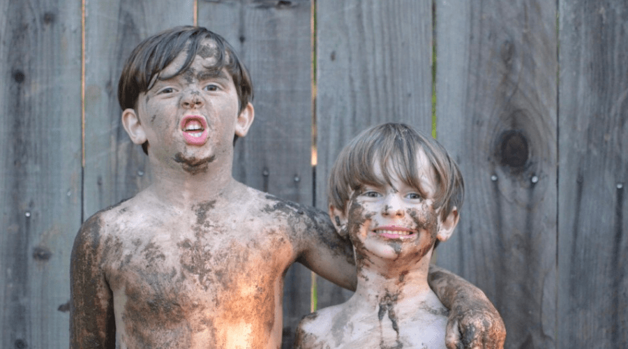two muddy boys standing in front of a fence