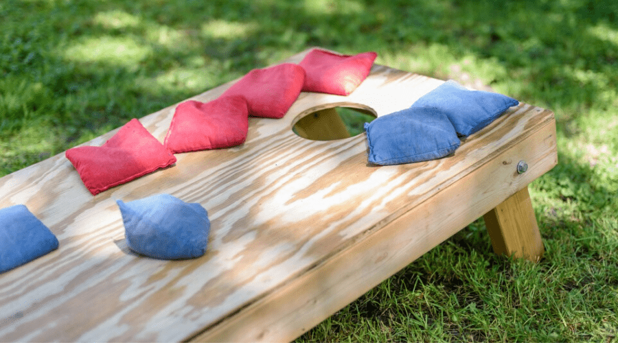 a sack toss or cornhole board and bags outdoors