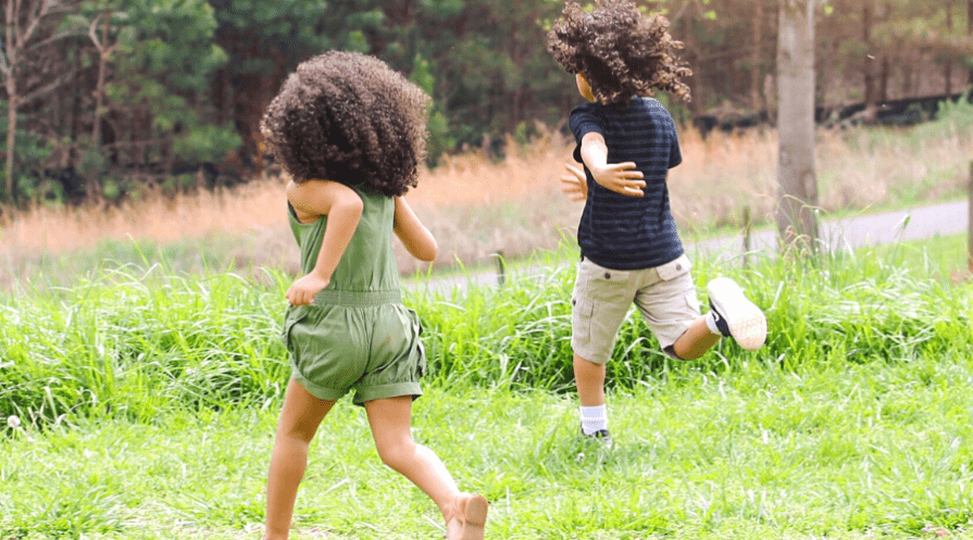 two kids running in tall grass
