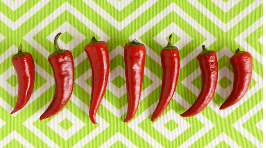 a row of red peppers on a green and white ground