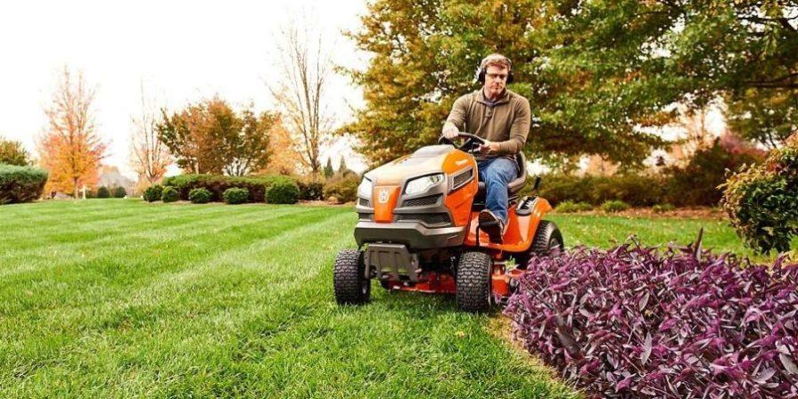 Man riding a Husqvarna YTH18542 riding lawn mower across his property.