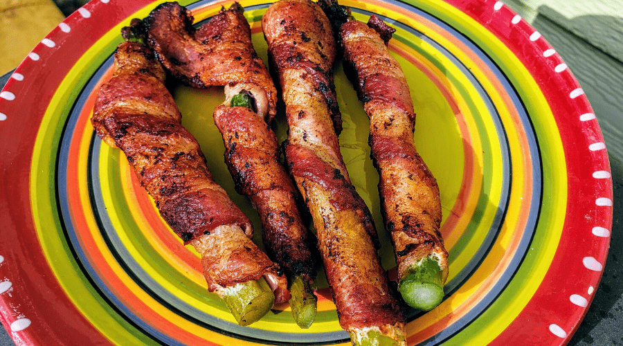 asparagus wrapped in bacon on colorful plate