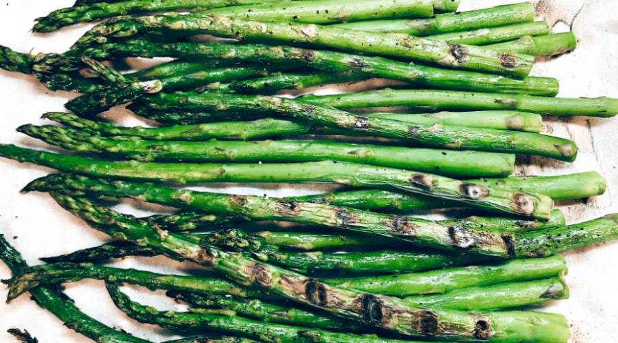 grilled asparagus on metal tray closeup