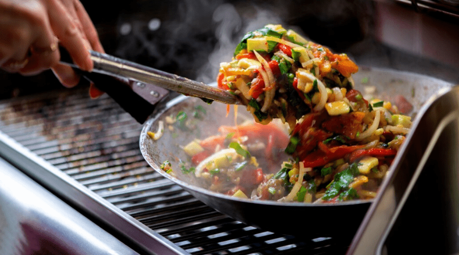 vegetables cooking in a saute pan on a gas grill outdoors