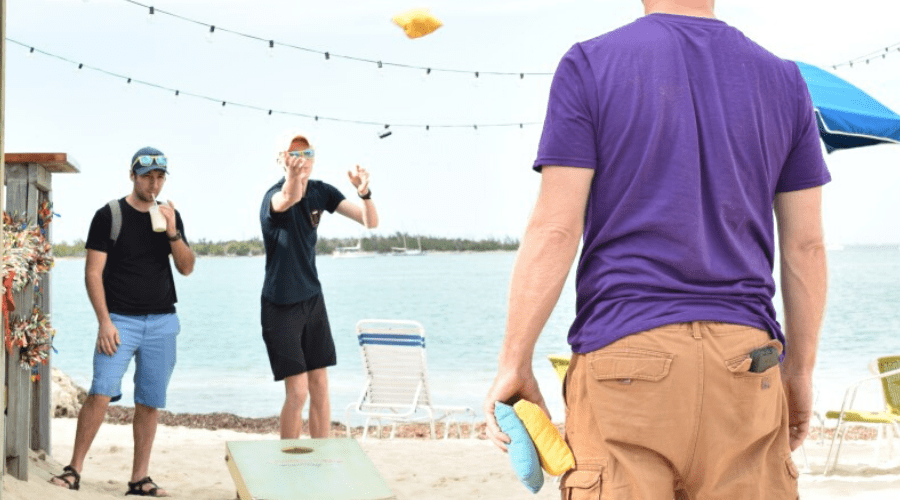 three men playing cornhole on a beach