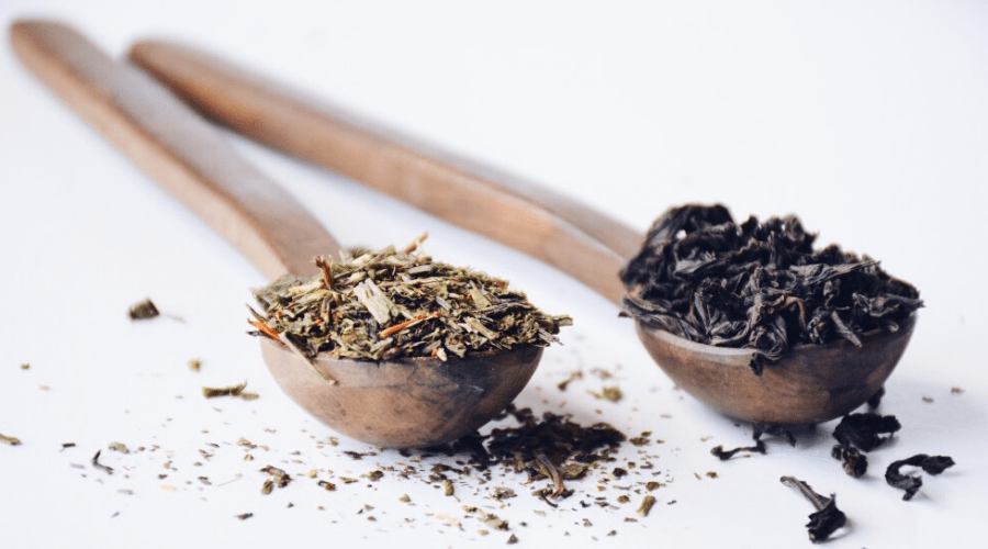 green and black teas in wooden spoons