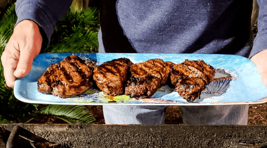 steaks on a platter from the grill outdoors