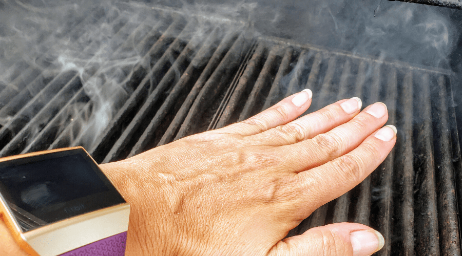 hand near warm grill to check temperature