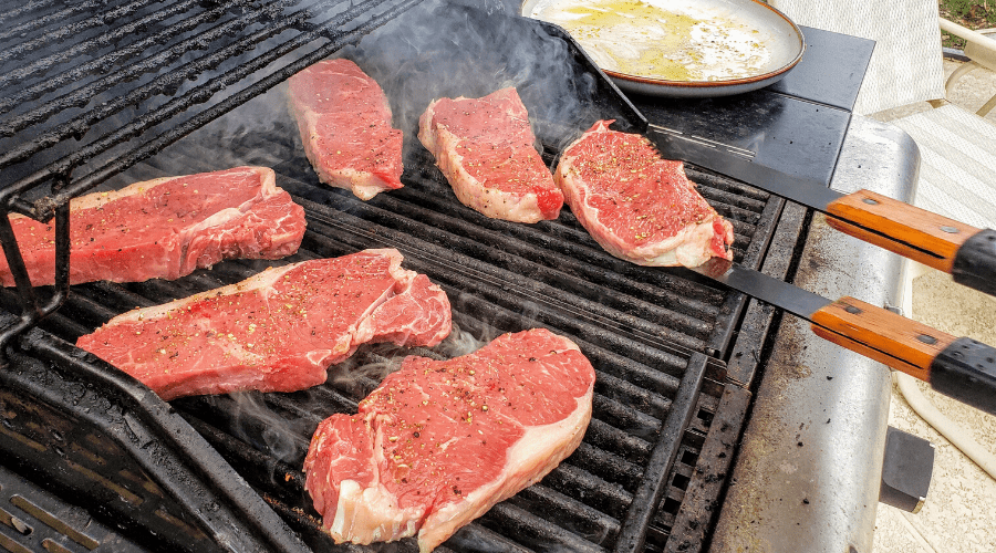 raw steaks on hot grill