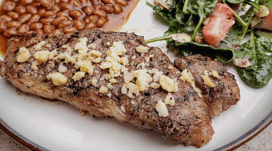 grilled steak on a plate with salad and beans