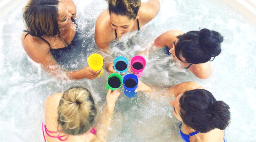 women in an inflatable hot tub drinking wine from colorful plastic cups