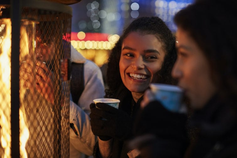 Girls drinking next to an outdoor propane heater