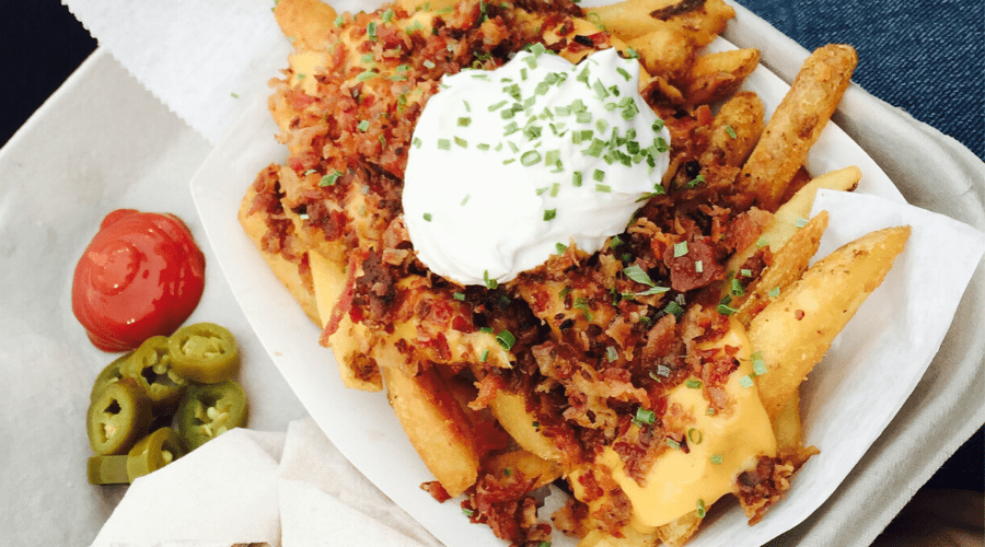 loaded fries with sour cream, bacon chives, cheese in a disposable box