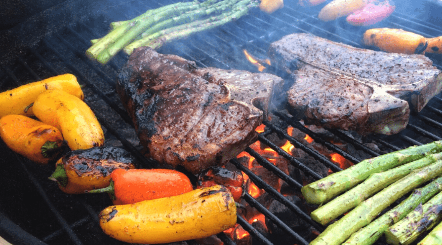 two steaks on a hot grill with peppers and asparagus