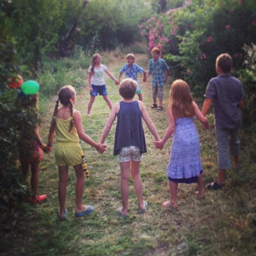 children in a circle playing red rover outdoors in clearing