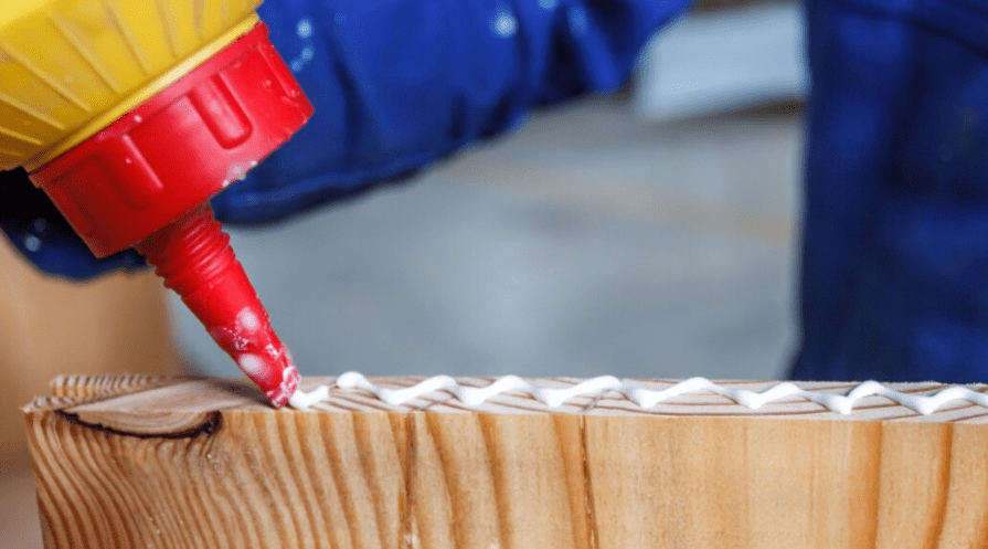 applying glue to a piece of unfinished wood
