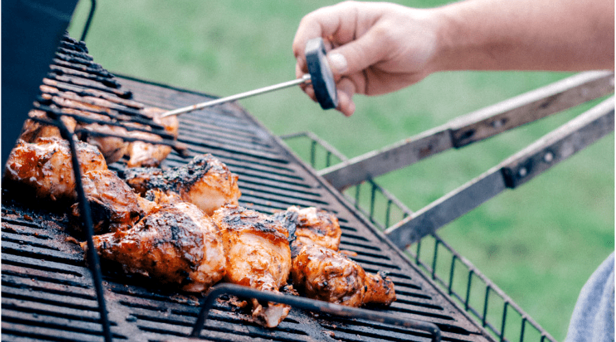 meat thermometer used to check temperature of chicken on a grill