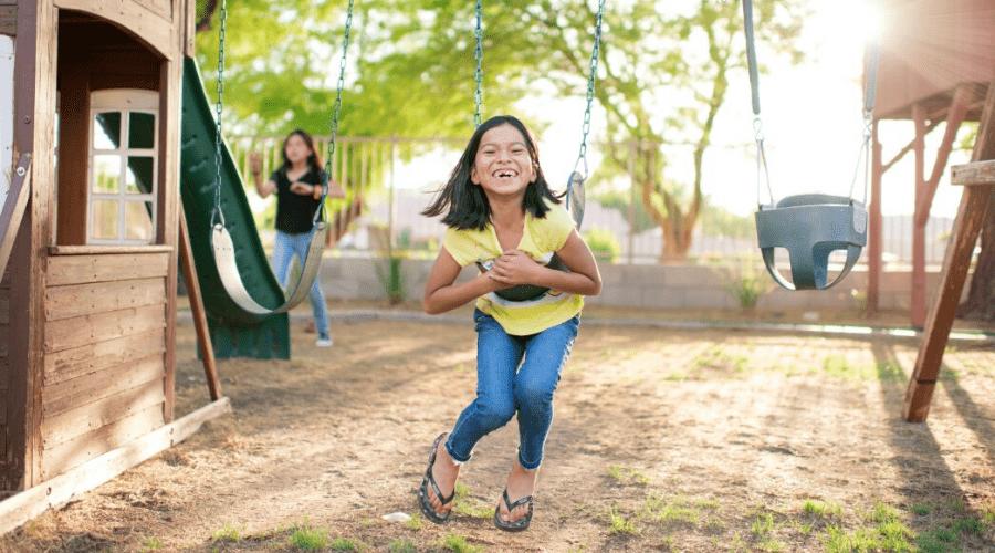 girl on swingset in backyard