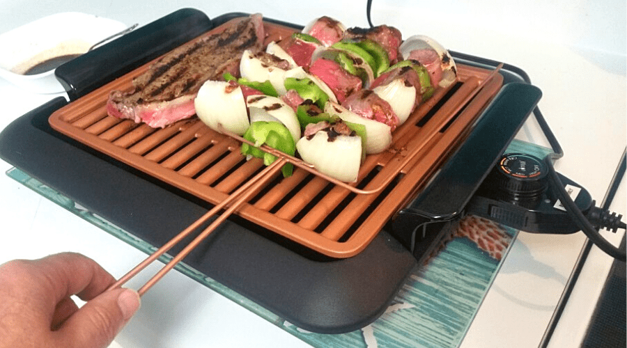 smokeless grill with meat and vegetable kebab skewers in use