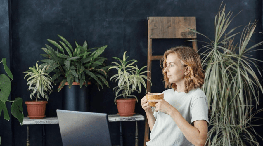 woman in room full of house plants shopping online drinking coffee