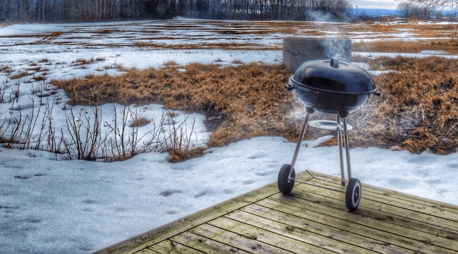 charcoal grill in use in winter on deck with snowy grass