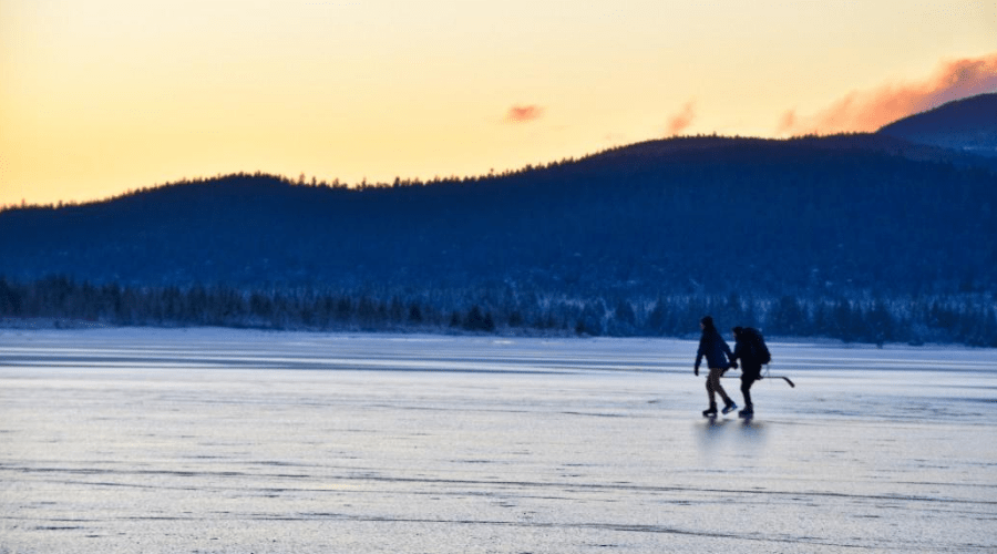 ice skating with hockey sticks on frozen lake in the morning