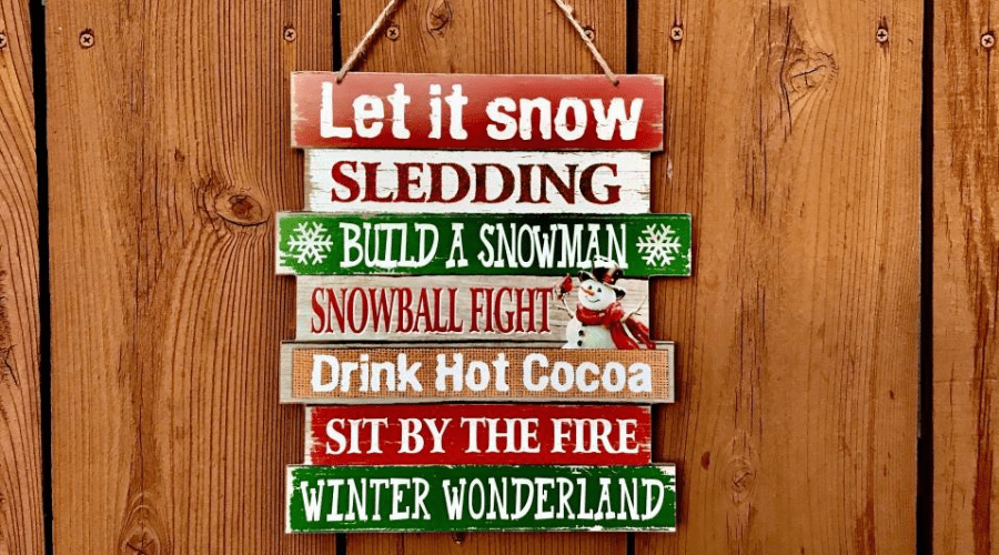 wooden sign for christmas against wood paneled surface