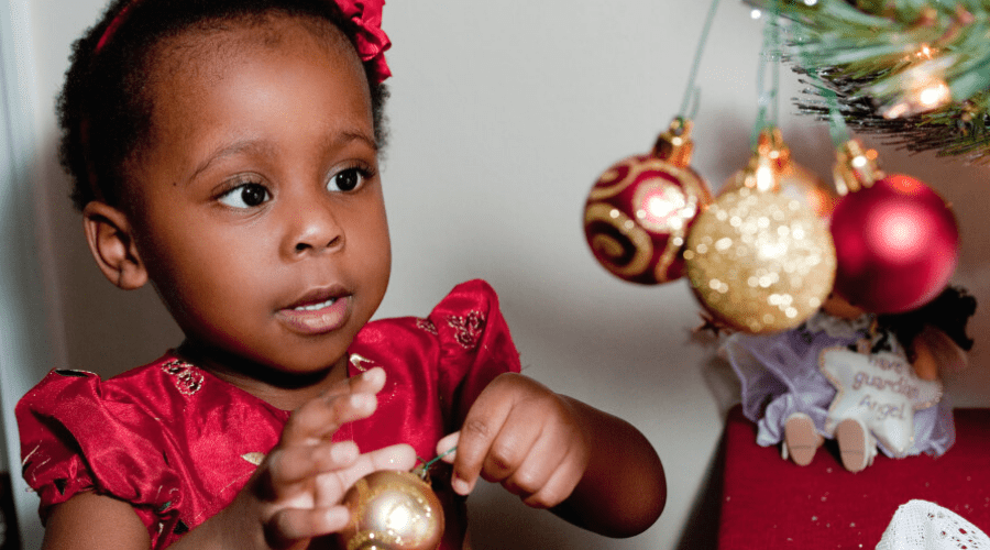 a small girl hangs an ornament to decorate a tree for indoor christmas fun