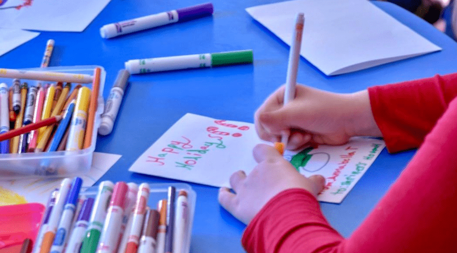 a child making christmas cards with paper and washable markers