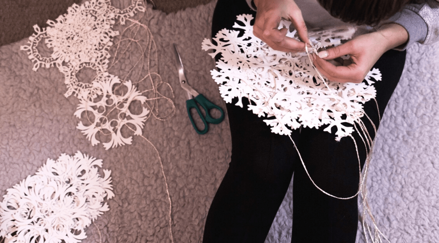 woman stringing handmade paper snowflakes onto twine for hanging