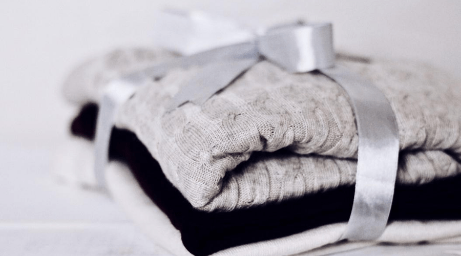 christmas gifts folded sweaters tied with silver fabric ribbon