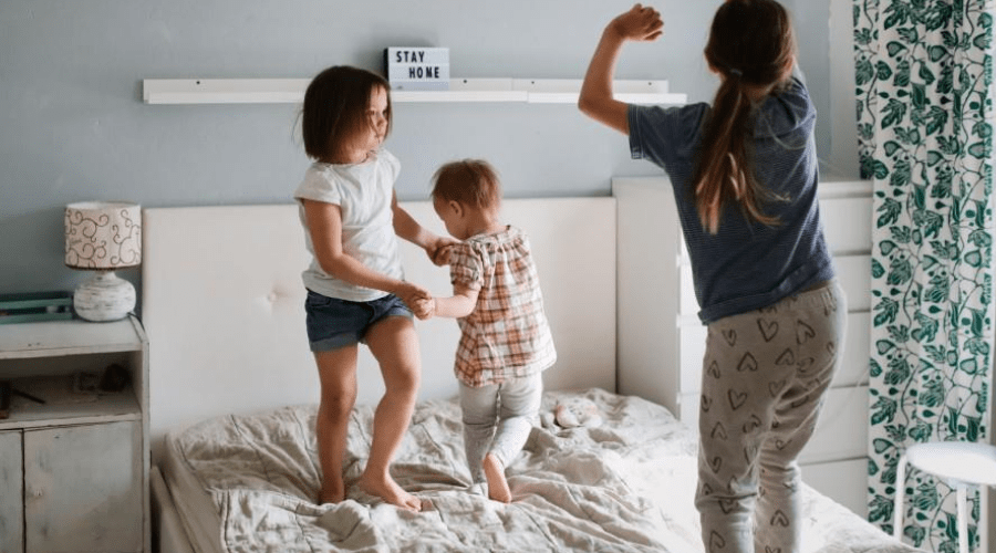 three kids dancing to christmas music on the bed