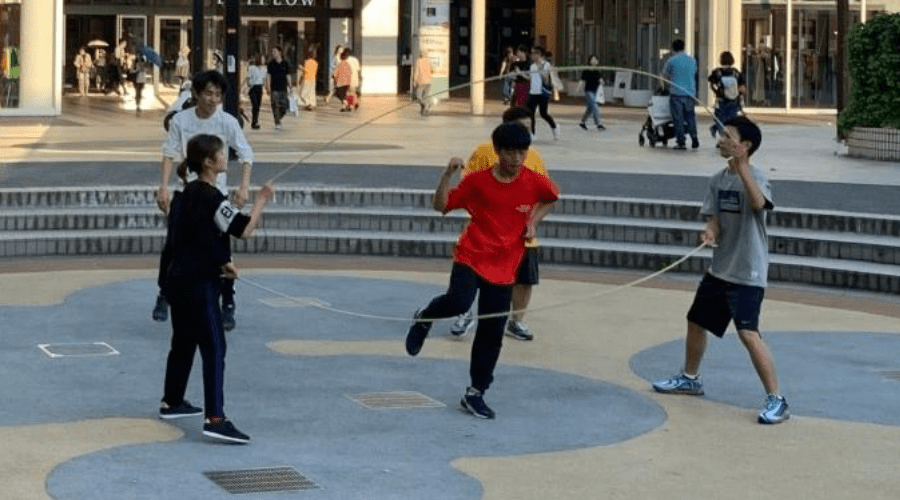 teens playing double dutch in a public park