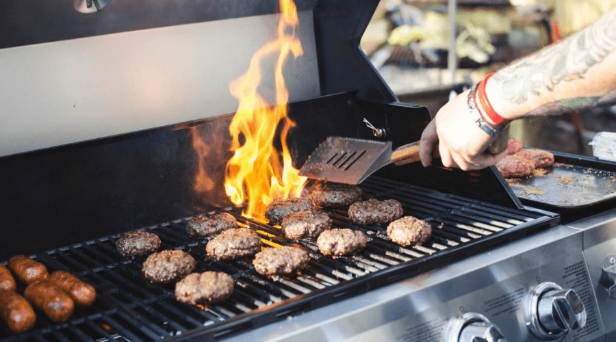 man cooking burgers on a propane gas grill