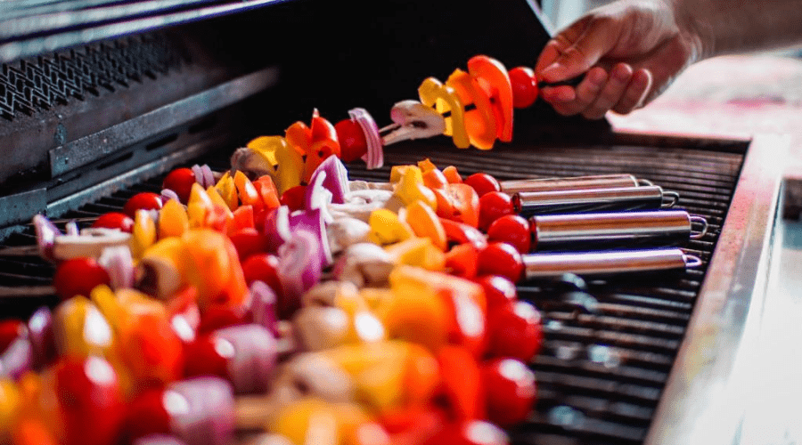 vegetable and meat skewer kebabs on a propane gas grill closeup