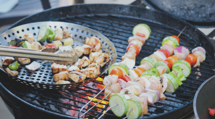 grill accessories in use grilling veggie skewers and meat in a basket and using tongs