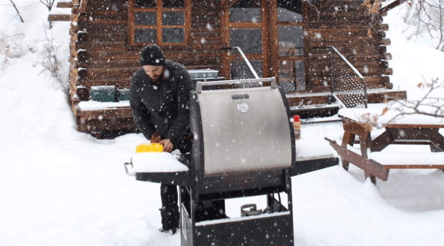 a man uses a propane grill in the snow outdoors near a cabin in winter