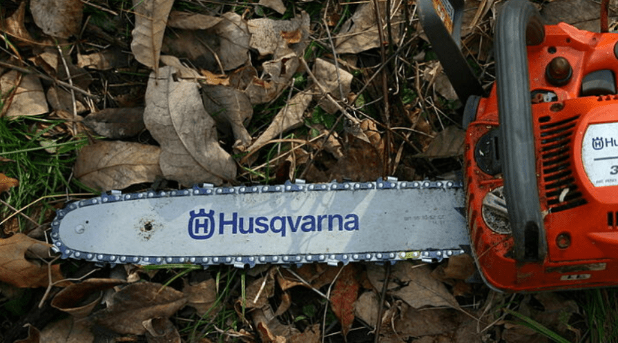 husqvarna chain saw lying in grass and leaves from above outdoors