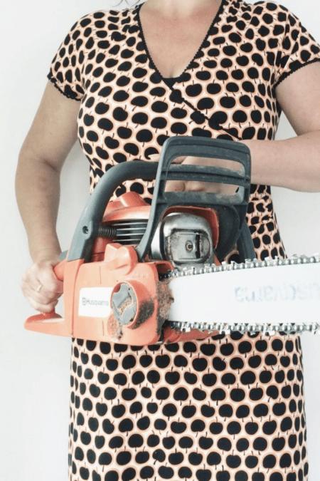 woman holding husqvarna chainsaw in polka dot dress indoors