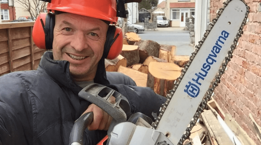 best chainsaw husqvarna man holding new saw in front of a pile of wood